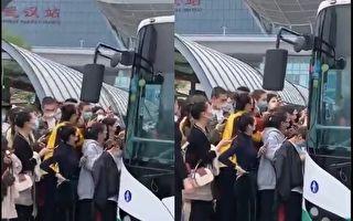 武汉火车站附近的公交车站处,不少人堵在一辆公交车门口,要准备上车。(视频截图)