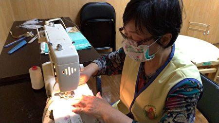 志工媽媽,戴起老花眼鏡,坐在裁縫機前縫製一個一個的布口罩。