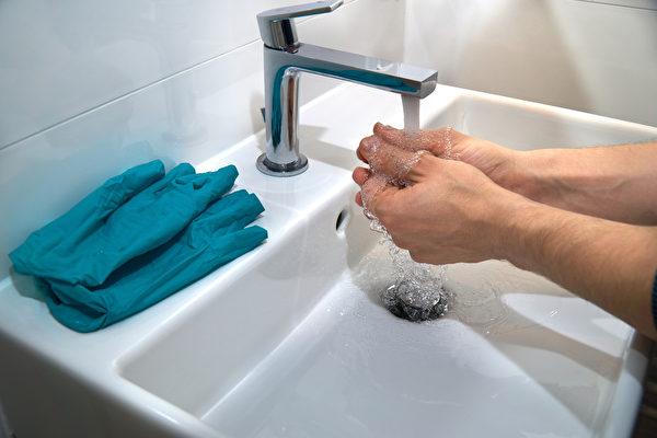 脱手套时,应从内向外翻脱,避免病毒碰处皮肤。戴前脱后都要洗手。(Shutterstock)