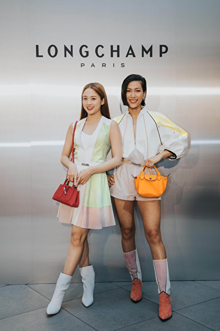 莫莉(右)选以拼接连身裤,搭配皮革长靴及橘色迷你手提包,绽放充沛活力;吴映洁身穿柔和色彩皮革连衣裙,衬托红色手提包。