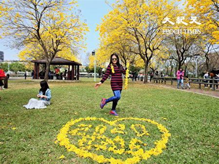 民眾開心地與地上撿拾風鈴花串成的花環、心形圖樣拍照。