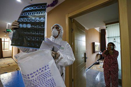 圖為武漢一處中共肺炎隔離病房門口,醫生在看病人的CT片子。(STR/AFP via Getty Images)