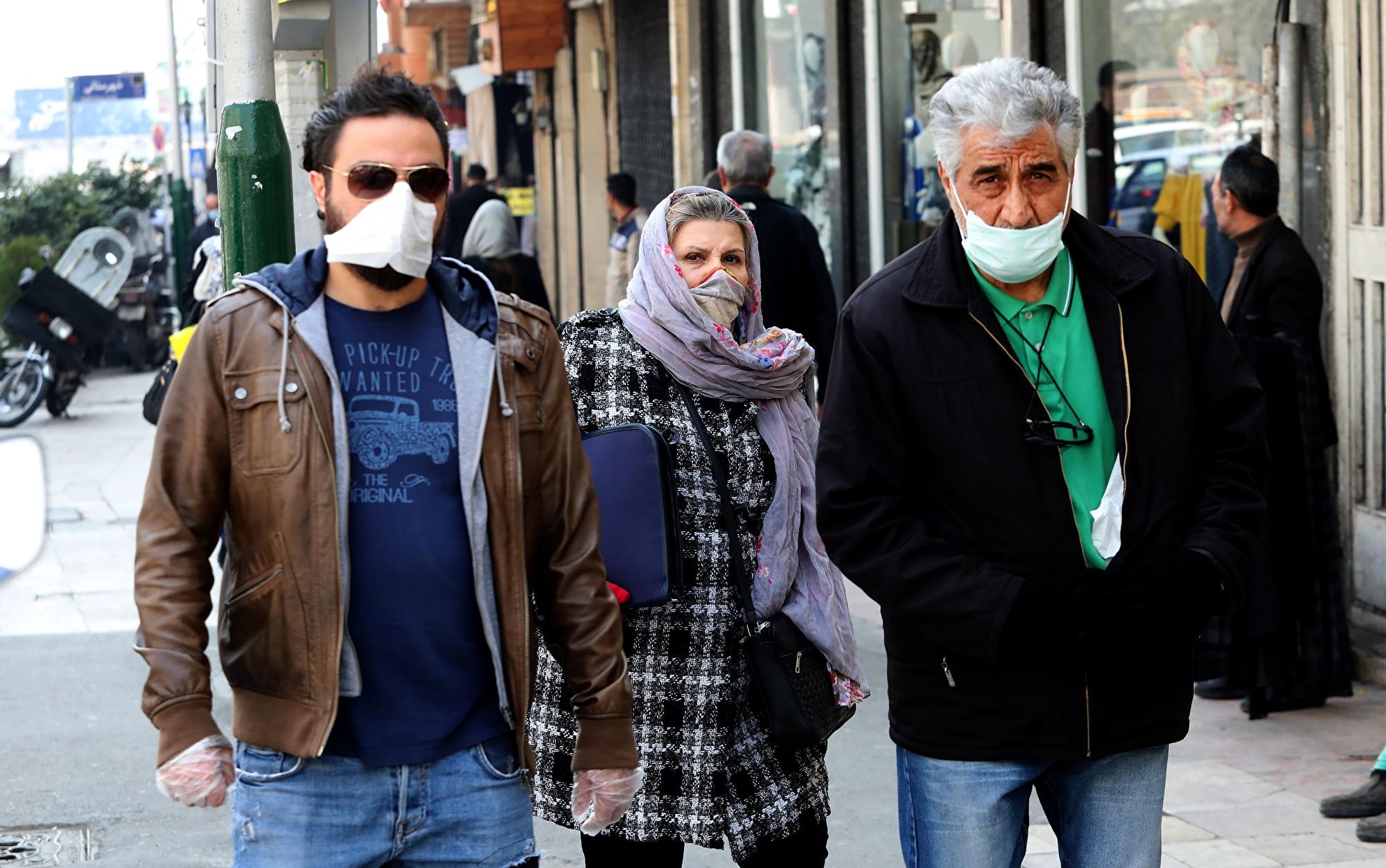 專家根據伊朗醫院披露的病例數推估,伊朗至少2.8萬人感染,大約是官方數據的9倍多。圖為2020年2月29日,中共肺炎疫情籠罩下的伊朗街頭行人。(ATTA KENARE/AFP)