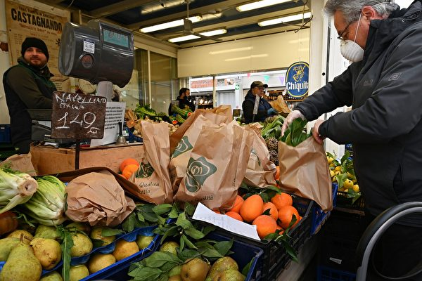 圖為意大利舉國封鎖令下的羅馬水果店,仍有客人買菜。(攝於2020年3月10日)(Alberto PIZZOLI / AFP)