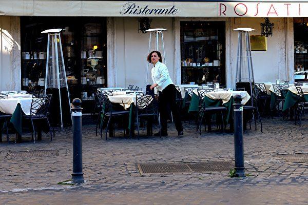 圖為意大利舉國封鎖令下羅馬街頭正在佈置餐桌的女侍。(攝於2020年3月10日)(Tiziana FABI / AFP)