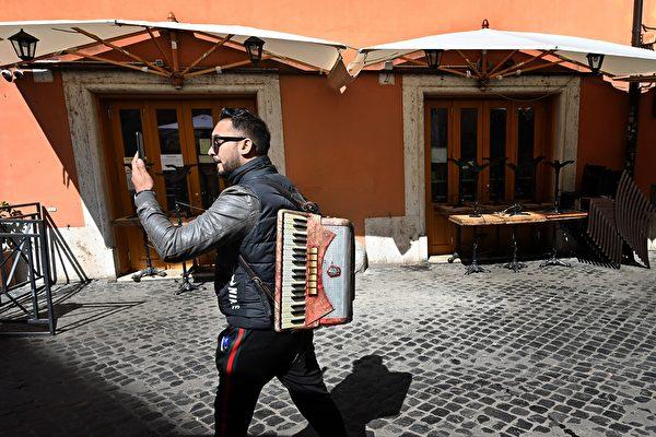 圖為意大利舉國封鎖令下的羅馬街頭藝人。(攝於2020年3月10日)(Vincenzo PINTO / AFP)
