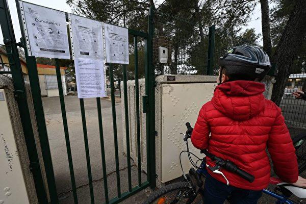 2020年3月12日,一個法國男孩在其關閉的學校的大門前閱讀關於武漢肺炎的信息。(PASCAL GUYOT/AFP via Getty Images)