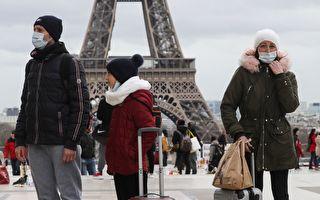 2020年3月12日,佩戴口罩的游客在巴黎的埃菲尔铁搭前。(Photo by LUDOVIC MARIN/AFP via Getty Images)