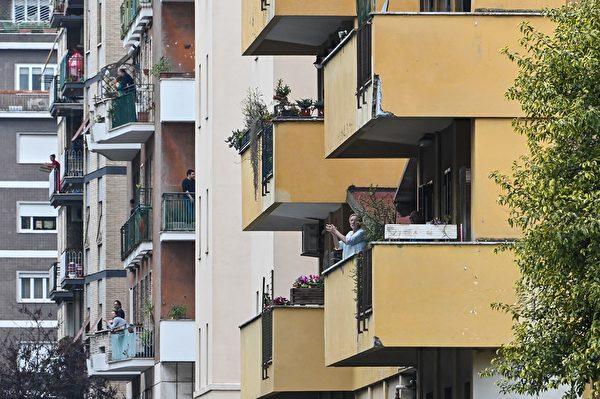為了控制中共肺炎疫情,意大利全國封城,民眾被要求禁止外出。圖為2020年3月15日,羅馬,民眾在陽台唱歌同樂。(TIZIANA FABI/AFP via Getty Images)