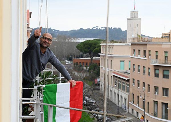 為了控制中共肺炎疫情,意大利全國封城,民眾被要求禁止外出。圖為2020年3月15日,羅馬,民眾在陽台掛上國旗加油打氣。(TIZIANA FABI/AFP via Getty Images)