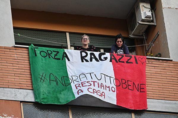 為了控制中共肺炎疫情,意大利全國封城,民眾被要求禁止外出。圖為2020年3月15日,羅馬,民眾在陽台掛上國旗加油打氣。(ANDREAS SOLARO/AFP via Getty Images)