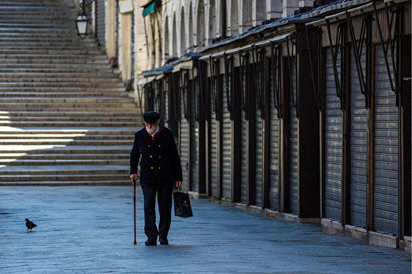 2020年3月18日,意大利威尼斯,在中共肺炎疫情下現正處於封城狀態。圖為一名戴著口罩的男子走過威尼斯一條空寂的街道。(ANDREA PATTARO/AFP via Getty Images)