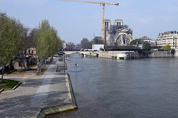 圖為3月20日的巴黎塞納河畔,對面是巴黎聖母院,修復工程已暫停。 (BERTRAND GUAY/AFP via Getty Images)