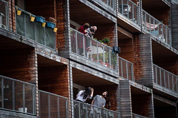 圖為3月20日,巴黎一棟住宅樓人們在自家陽台向鄰居打招呼。(MARTIN BUREAU/AFP via Getty Images)