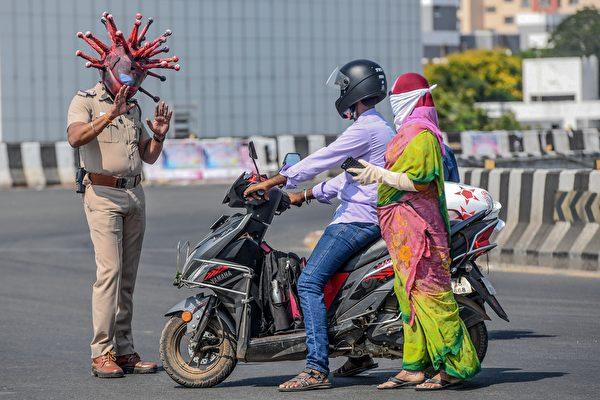 2020年3月28日,印度清奈一名警察戴著病毒狀安全帽,警告民眾待在家裏,不要外出。(ARUN SANKAR/AFP via Getty Images)