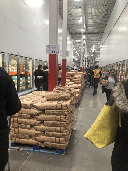 圖:溫哥華各地突顯搶購風,一些民眾擔憂新冠肺炎擴大,圖為商家將米麵擺放在走道上。(邱晨/大紀元)
