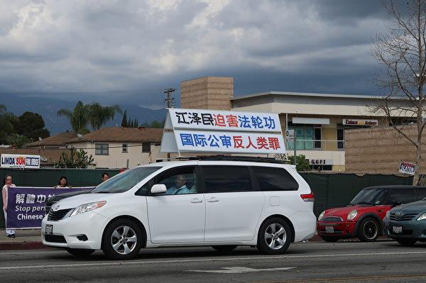 2020年3月7 日(周六),「真相車隊」載著「法輪大法 宏傳世界各國」的看板於聖蓋博市的夏威夷超市附近遊行。(徐繡惠/大紀元)