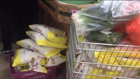 華人在法拉盛昌發超市搶購大米,有的人一買就至少5大包。(影片截圖)