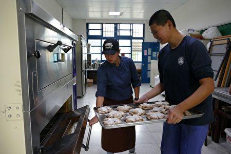 特教班学生在竹山国中阳光小竹烘焙坊将面包送入烤炉。
