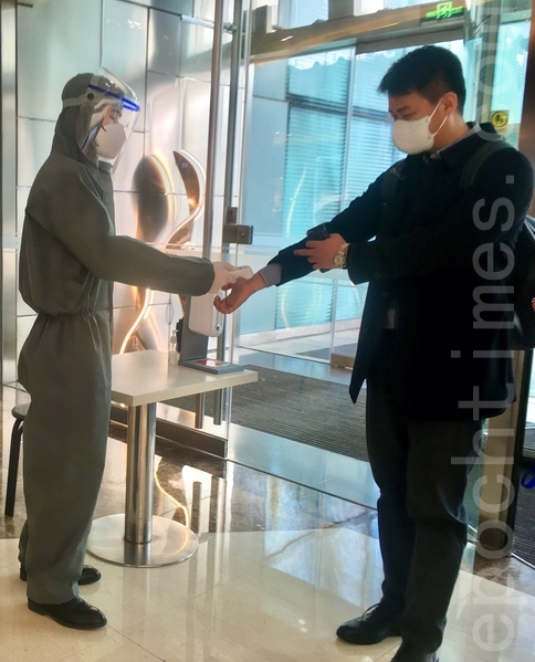 3月31日,北京CBD金地中心門口「全副武裝」的檢測人員。(大紀元)
