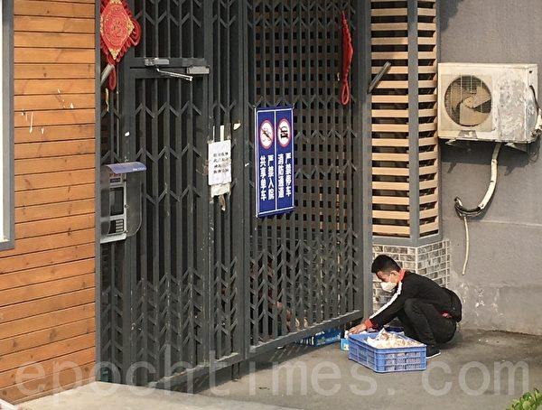 3月30日,外賣員需隔著鐵柵門送貨。(大紀元)