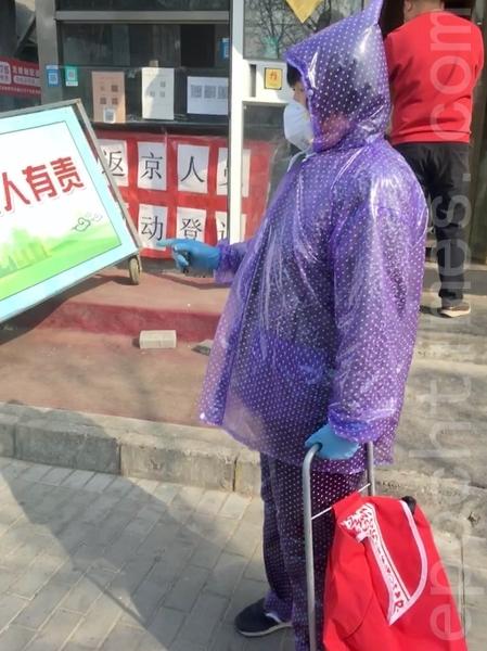 3月29日,北京街頭,身著自製隔離服購物的民眾。(大紀元)