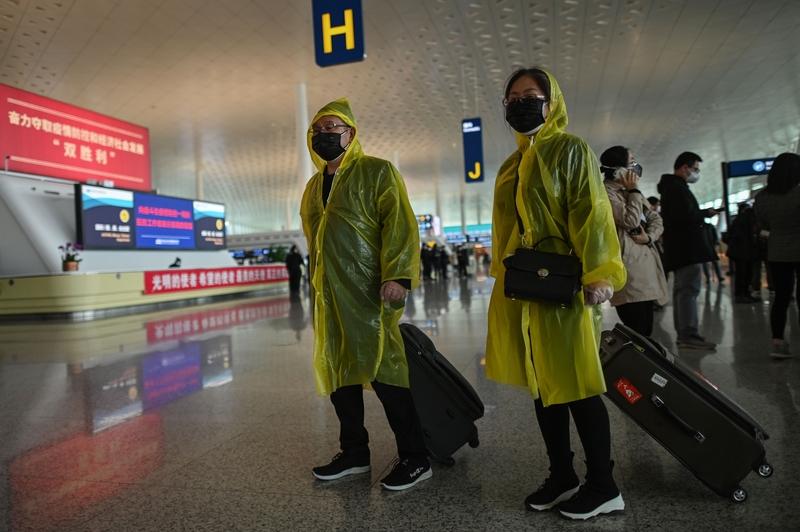 2020年4月8日,湖北武漢,武漢天河機場內準備搭機的民眾全副武裝。(HECTOR RETAMAL/AFP via Getty Images)