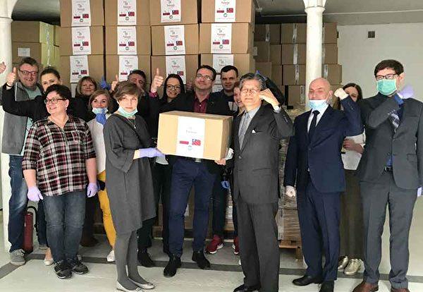 台灣捐贈的50萬片外科口罩10日上午運抵波蘭,由駐波蘭代表施文斌(右)轉交給波蘭官員。(駐波蘭代表處提供/中央社)