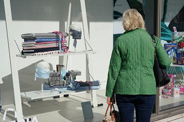 2020年4月22日,一名婦女看著百貨商店櫥窗裏製作DIY口罩的材料。(Sean Gallup/Getty Images)