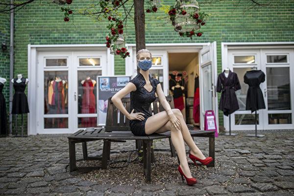 自2020年3月在德國柏林爆發中共病毒以來,這家時裝店首次開張,在店前模特兒也戴上了時尚的防護口罩。( Maja Hitij/Getty Images)