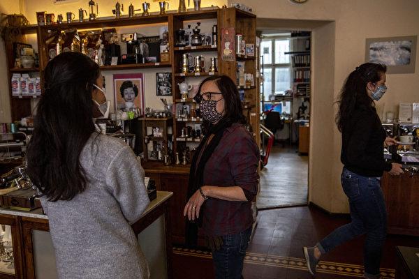 自2020年3月,德國柏林出現中共病毒大流行以來,4月22日這家咖啡店首次營業,店主戴著防護口罩為客戶服務。(Maja Hitij/Getty Images)