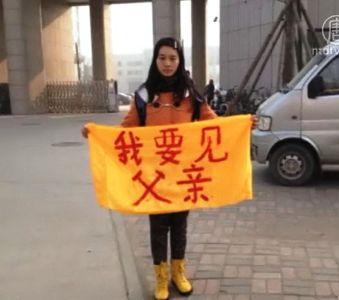 2014年3月12日,卞麗潮23歲的女兒卞曉暉為救父親在石家莊監獄門口舉起橫幅「我要見父親」。(明慧網)