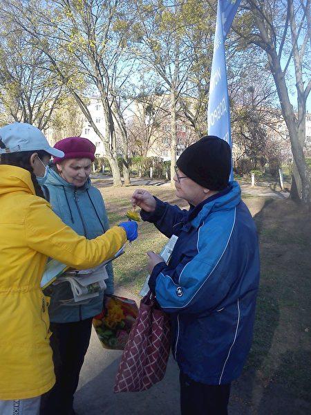哈爾科夫市民經過煉功場地時和法輪功學員交談,並接過學員贈送的小蓮花。(明慧網)