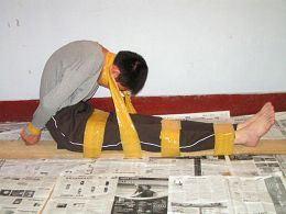 中共勞教所酷刑演示:捆綁。(明慧網)