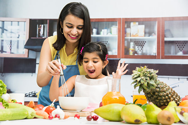 Mother and daughter cook together. (Shutterstock)