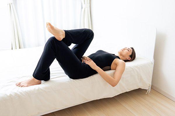 """让你早晨起床后摆脱疲劳的""""不动零位训练""""动作一:仰躺在床的左边,左膝立起,再将右脚跟靠在左膝上。(采实文化提供)"""