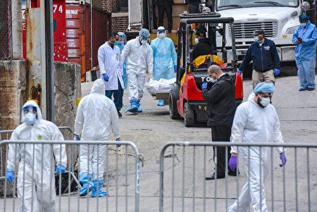 紐約市因中共病毒(武漢肺炎)引起的死亡人數激增,多家醫院外都放置了冷藏卡車作為臨時停屍房。圖為布碌崙醫務人員在醫院外搬運屍體。
