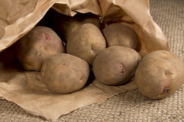 将马铃薯装入纸袋,并在中间放一颗苹果,可以避免马铃薯发芽。(Shutterstock)