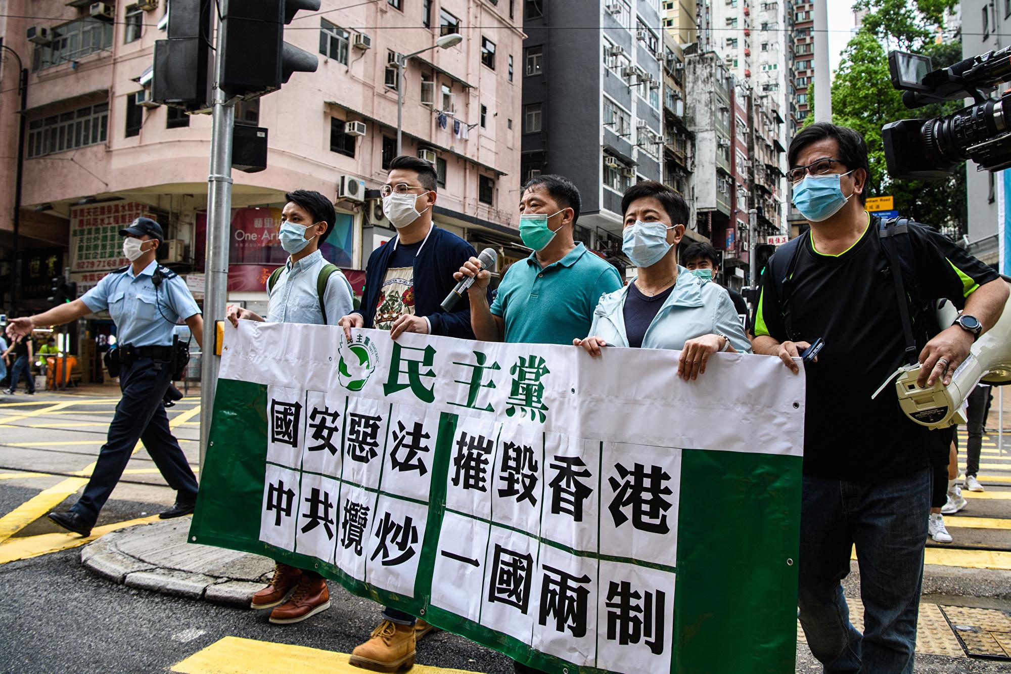 圖為香港民主抗議人士5月22日拿著標語牌,抗議中共對香港強加國安法。(Anthony WALLACE / AFP)