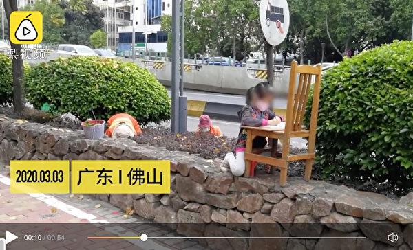 小女孩坐在路邊上網課。(影片截圖)