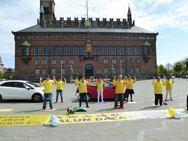 5月9日,丹麥部份法輪功學員在哥本哈根市政廳廣場上集體煉功。(明慧網)