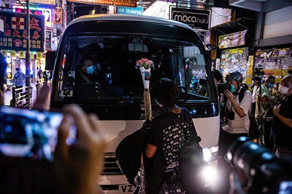 5月10日,香港市民在商場等地抗議。一位女士拿著一束母親節鮮花站在防暴警察車子前面。( ISAAC LAWRENCE/AFP via Getty Images)
