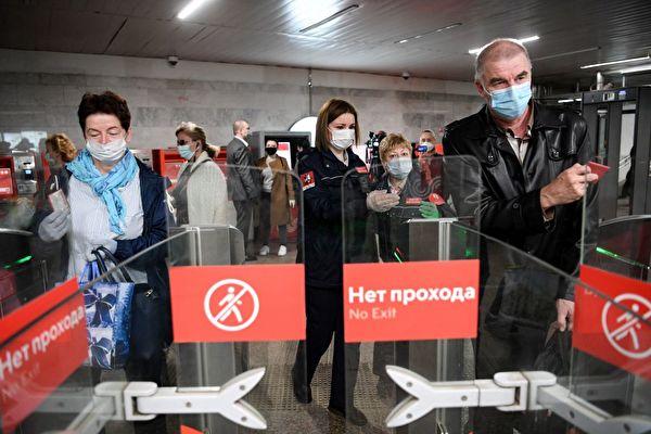 2020年5月12日,莫斯科一處地鐵站,市民戴著口罩經過檢票口。 (Photo by KIRILL KUDRYAVTSEV/AFP via Getty Images)