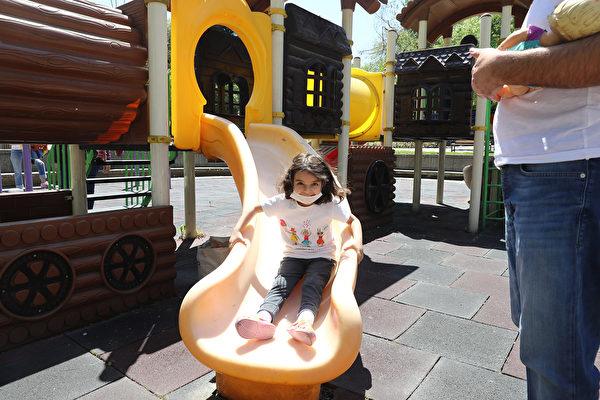 2020年5月13日,土耳其安卡拉,土耳其為了防疫,規定14歲以下兒童准許在上午11點到下午3點之間出門,但是要保持社交距離並戴上口罩。圖為兒童在公園玩耍。(ADEM ALTAN/AFP via Getty Images)