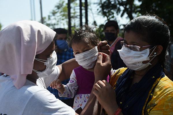 2020年5月14日,印度,在政府放寬全國禁閉措施之後,一名滯留的移工準備和其他工人一起登上公共汽車前,為一位小嬰兒調整了口罩。(SAM PANTHAKY/AFP via Getty Images)