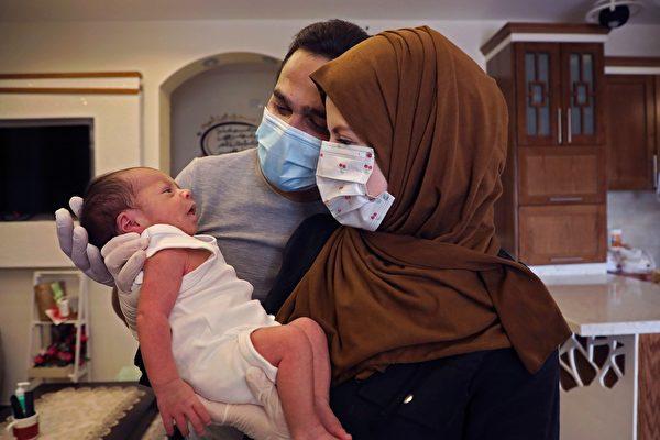 2020年5月17日,巴勒斯坦al-Dahriya村,感染中共病毒後康復的巴勒斯坦人Alaa和Tasneem al-batat抱著新生嬰兒Tayem。(HAZEM BADER/AFP via Getty Images)