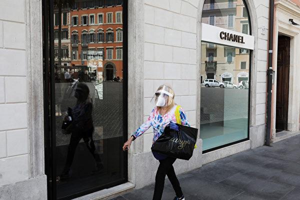 2020年5月19日,意大利羅馬,戴著防護面罩的婦女經過香奈兒商店。(Marco Di Lauro/Getty Images)