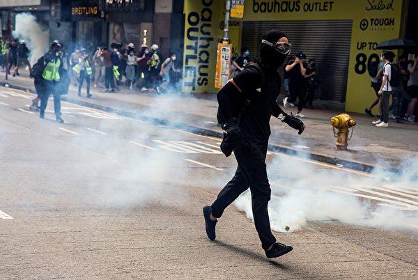 2020年5月24日,香港反国安法游行。防暴警察施放催泪弹,市民避走。( ISAAC LAWRENCE/AFP via Getty Images)