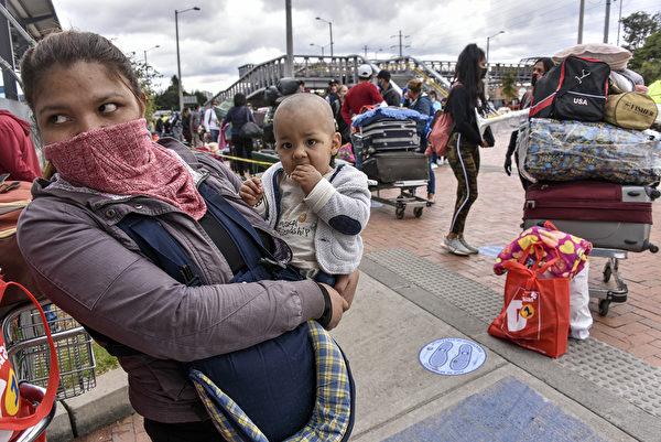2020年5月15日,哥倫比亞波哥大,因中共病毒大流行,委內瑞拉移民Floricarmen Araujo在波哥大北部巴士站外與她的孩子等著買公車票。(Guillermo Legaria/Getty Images)
