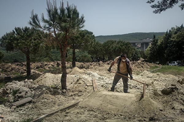 2020年5月16日,土耳其伊斯坦布爾,一名墓地工人將泥土鏟到阿卜杜拉·比伯(Abdullah Biber)的墳墓上,他死於中共病毒,他葬於Kilyos墓地內的專用中共病毒亡者埋葬地。(Chris McGrath/Getty Images)